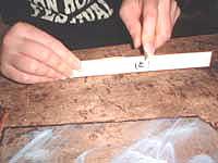 ⑥テープを木の棒(フィード)で押さえガラスとテープの間の空気を抜きます